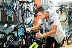Muchacho que busca y que intenta la nueva bicicleta que compite con Fotografía de archivo libre de regalías