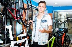 Muchacho que busca y que intenta la nueva bicicleta que compite con Fotografía de archivo