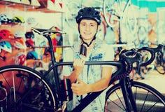 Muchacho que busca y que intenta la nueva bicicleta que compite con Imagenes de archivo