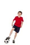 Muchacho que camina en balón de fútbol Fotografía de archivo