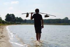 Muchacho que camina en el agua en luz trasera Imagenes de archivo