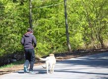 muchacho que camina en el camino en el bosque con un perro Fotos de archivo libres de regalías