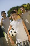 Muchacho (13-15) que celebra el balón de fútbol con cuatro hombres en el parque. Foto de archivo libre de regalías