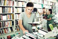 Muchacho que celebra el libro y la mirada Foto de archivo libre de regalías