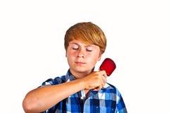 Muchacho que cepilla su pelo Foto de archivo libre de regalías