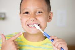 Muchacho que cepilla sus dientes y señalar Imagen de archivo