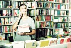 Muchacho que charla en el teléfono móvil y que busca el libro Fotografía de archivo libre de regalías