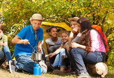 Muchacho que cocina la sopa en el pote para los amigos en el sitio para acampar Imagen de archivo libre de regalías