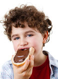 Muchacho que come el bocadillo con crema del chococolate Foto de archivo libre de regalías