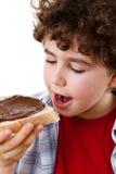 Muchacho que come el bocadillo con crema del chococolate Imagenes de archivo