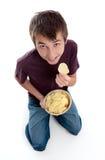 Muchacho que come el bocado de la viruta de la patata a la inglesa de patata Imagen de archivo libre de regalías