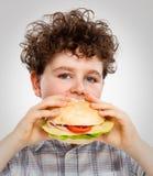 Muchacho que come el emparedado grande Foto de archivo