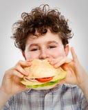 Muchacho que come el emparedado grande Fotos de archivo