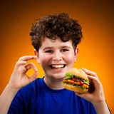 Muchacho que come el emparedado grande que muestra la muestra ACEPTABLE Imagen de archivo libre de regalías