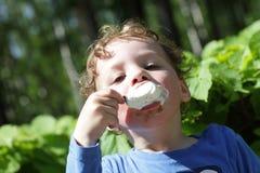 Muchacho que come el helado al aire libre fotos de archivo