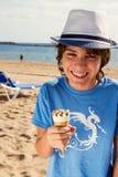 Muchacho que come el helado en la playa Imagenes de archivo