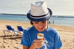 Muchacho que come el helado en la playa Foto de archivo