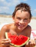 Muchacho que come el melón en una playa Imagenes de archivo