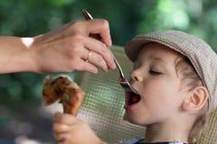 Muchacho que come el pollo Fotos de archivo libres de regalías
