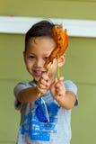 Muchacho que come el pollo asado a la parrilla Fotos de archivo