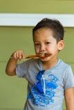 Muchacho que come el pollo asado a la parrilla Foto de archivo