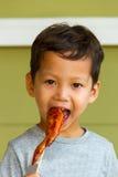 Muchacho que come el pollo asado a la parrilla Foto de archivo libre de regalías