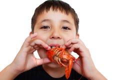muchacho que come juguetónamente los cangrejos Imagen de archivo