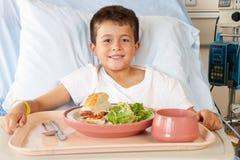 Muchacho que come la comida en cama de hospital Fotos de archivo libres de regalías