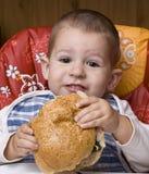 Muchacho que come la hamburguesa Imagen de archivo