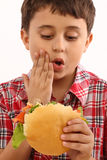 Muchacho que come la hamburguesa Fotografía de archivo