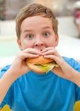 Muchacho que come la hamburguesa Fotos de archivo
