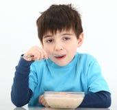 Muchacho que come la harina de avena fotos de archivo