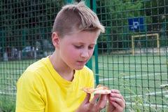 Muchacho que come la pizza al aire libre Fotos de archivo libres de regalías