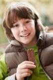 Muchacho que come la ropa del invierno de la barra de chocolate que desgasta Foto de archivo