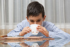 Muchacho que come la sopa en la tabla de cocina Foto de archivo libre de regalías