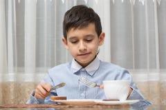 Muchacho que come la sopa en la tabla de cocina Imagenes de archivo