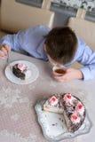 Muchacho que come la torta en la tabla Imagen de archivo libre de regalías