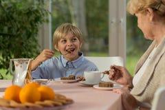 Muchacho que come la torta sabrosa Imagen de archivo libre de regalías