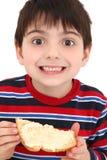 Muchacho que come la tostada y la mantequilla foto de archivo libre de regalías
