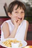 Muchacho que come las fritadas Fotografía de archivo