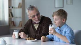 Muchacho que come las galletas con la leche, compartiendo con las noticias de abuelo de la guardería almacen de video