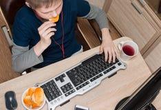 Muchacho que come las patatas fritas y que practica surf en Internet o que juega el vid Foto de archivo
