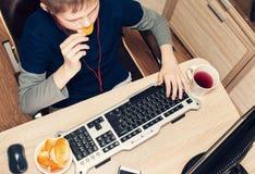Muchacho que come las patatas fritas y que practica surf en Internet o que juega el vid Fotos de archivo libres de regalías