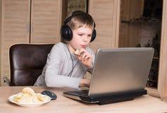 Muchacho que come las patatas fritas y que practica surf en Internet o que juega el vid Imagen de archivo