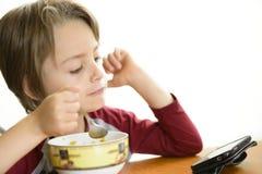 Muchacho que come los cereales Imagenes de archivo