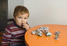Muchacho que come los chocolates fotos de archivo libres de regalías