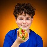 Muchacho que come los emparedados grandes Fotos de archivo