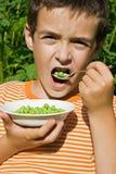Muchacho que come los guisantes Imagen de archivo libre de regalías