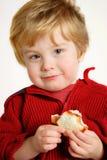 Muchacho que come un emparedado de la mantequilla y de la jalea de cacahuete Fotos de archivo
