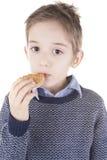 Muchacho que come una galleta Imágenes de archivo libres de regalías